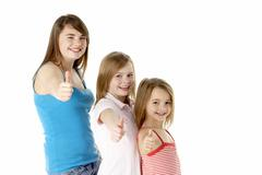 Three Girls Giving Thumbs Up Gesture In Studio - stock photo