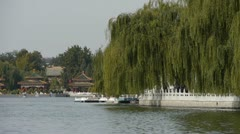 China Beijing ancient architecture Beihai Park & boat reflected on lake water. Stock Footage