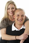 Studio Portrait Of Young Couple Hugging - stock photo