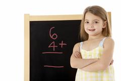 Young Girl Looking Thoughtful Next To Blackboard - stock photo