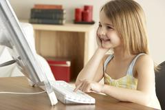 Young Girl Using Computer At Home - stock photo