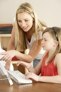 Mother And Daughter At Home Using Computer - stock photo