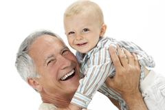 Studio Portrait Of Grandfather Holding Grandson - stock photo