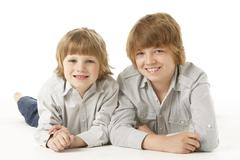 Two Young Boys Lying On Stomach In Studio - stock photo