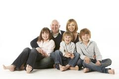 Studio Shot Of Family Group Sitting In Studio - stock photo