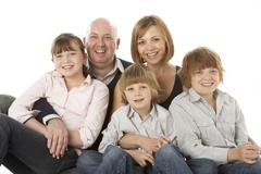 Studio Shot Of Family Group Sitting In Studio Stock Photos
