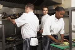 Team Of Chefs Preparing Food In Restaurant Kitchen - stock photo