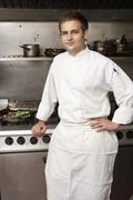 Male Chef Standing Next To Cooker In Restaurant Kitchen - stock photo