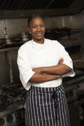Female Chef Standing Next To Cooker In Restaurant Kitchen Stock Photos
