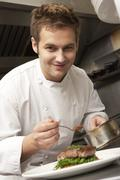 Chef Adding Sauce To Dish In Restaurant Kitchen Stock Photos