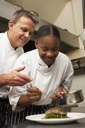 Chef Instructing Trainee In Restaurant Kitchen - stock photo