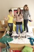 Group Of Teenage Girls Hanging Out In Untidy Bedroom - stock photo