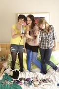 Group Of Teenage Girls Hanging Out In Untidy Bedroom Stock Photos