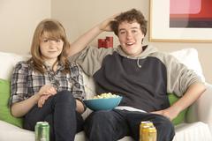 Teenage Couple Sitting On Sofa Watching TV Stock Photos