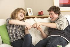 Teenage Couple Arguing Over TV Remote Stock Photos