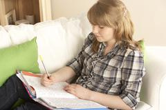 Teenage Girl Studying At Home Sitting On Sofa Stock Photos