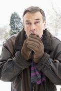 Senior Man Standing Outside In Snowy Landscape Warming Hands Stock Photos