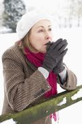 Senior Woman Standing Outside In Snowy Landscape Warming Hands Stock Photos