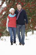 Senior Couple Walking Through Snowy Woodland - stock photo