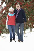 Senior Couple Walking Through Snowy Woodland Kuvituskuvat