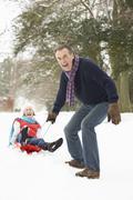 Senior Couple Sledging Through Snowy Woodland - stock photo