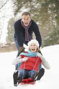 Senior Couple Sledging Through Snowy Woodland Stock Photos