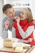 Senior Couple Making Sandwich In Kitchen - stock photo