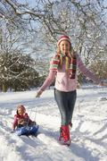 Mother Pulling Daughter On Sledge Through Snowy Landscape - stock photo