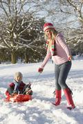 Mother Pulling Son On Sledge Through Snowy Landscape Stock Photos