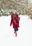Woman Walking Through Snowy Woodland - stock photo