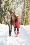 Couple Walking Through Snowy Woodland Stock Photos