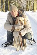 Man Walking Dog Through Snowy Woodland Stock Photos