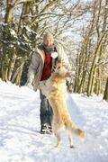 Man Walking Dog Through Snowy Woodland - stock photo