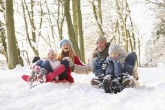 Family Sledging Through Snowy Woodland - stock photo