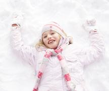 Girl Laying On Ground Making Snow Angel - stock photo