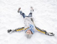 Boy Laying On Ground Making Snow Angel - stock photo