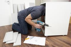 Stock Photo of Man Assembling Flat Pack Furniture