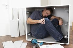 Stock Photo of Man Trapped Whilst Assembling Flat Pack Furniture