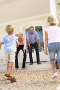 Grandparents Welcoming Grandchildren On Visit To Home Stock Photos