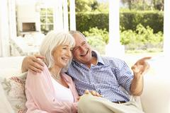Portrait Of Senior Couple Relaxing Together On Sofa - stock photo