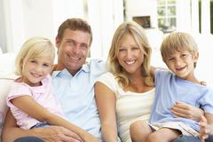 Portrait Of Young Family Relaxing Together On Sofa Stock Photos
