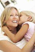 Daughter Giving Mother Kiss Relaxing On Sofa - stock photo