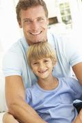 Portrait Of Father And Son Relaxing On Sofa Stock Photos