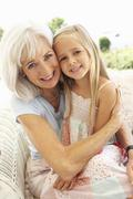 Portrait Of Grandmother With Granddaughter Relaxing Together On Sofa Stock Photos