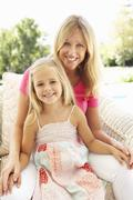 Portrait Of Mother And Daughter Relaxing On Sofa - stock photo