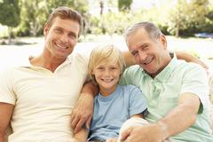 Portrait Of Grandfather, Son And Grandson Relaxing On Sofa - stock photo