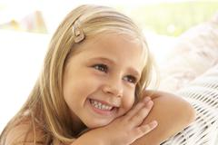 Portrait Of Young Girl Relaxing On Sofa Stock Photos