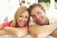 Portrait Of Young Couple Relaxing Together On Sofa Stock Photos