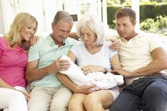 Extended Family Relaxing Together On Sofa With Newborn Baby - stock photo