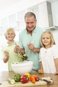 Grandchildren Helping Grandfather To Prepare Salad In Modern Kitchen - stock photo